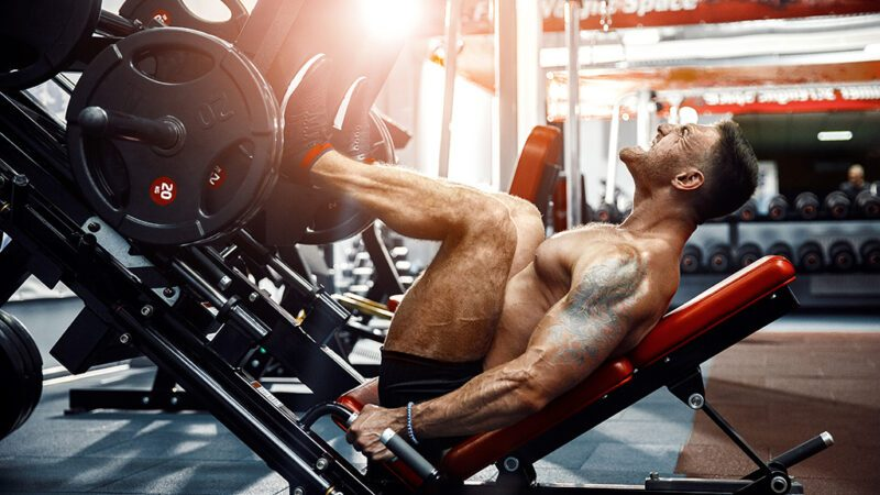 sports performance progressive overload - guy using weights for legs