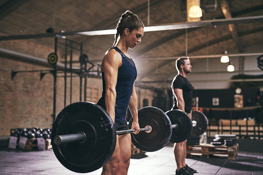 the power of progressive overload for sports performance - woman and man lifting weights